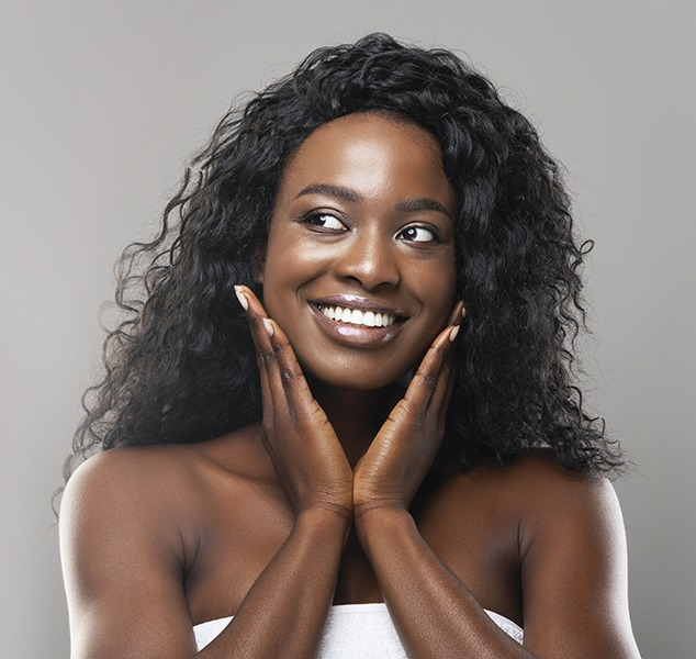 Dark skinned woman with nice skin feeling face, smiling