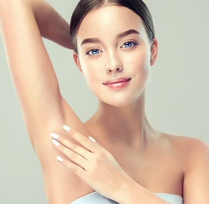 Woman with clean underarms, no hair, smiling softly with hand feeling underarm