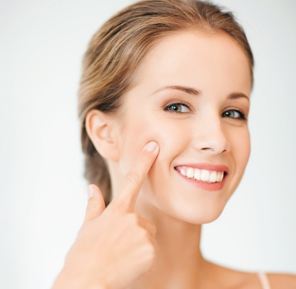 Woman pointing to cheek without wrinkles, smiling