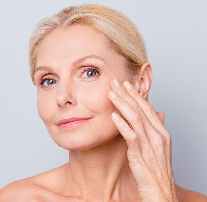 Older mature woman feeling her cheek with hand, smooth skin on her face